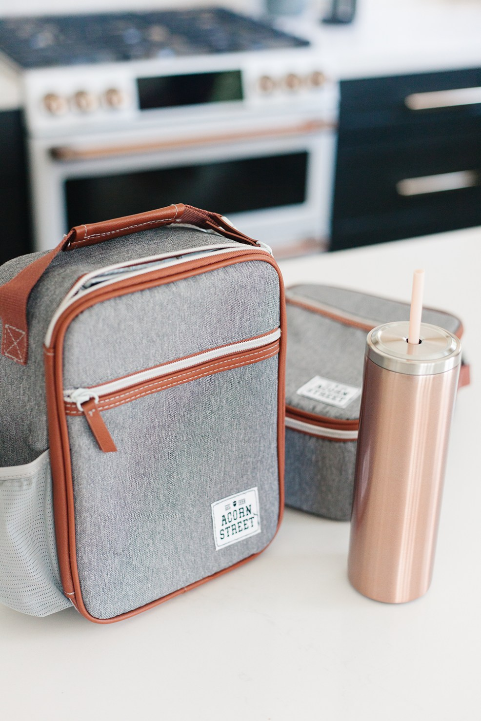 Wow and Now by popular US life an style blog, E. Interiors Design: image of a Wow and Now Acorn Street lunch box and Wow and Now rose gold tumbler.
