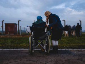 Nachbarschaftshelferin neben einer Person im Rollstuhl
