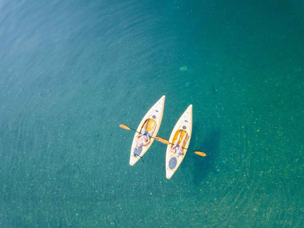 bird s eye view of two people canoeing on body of water