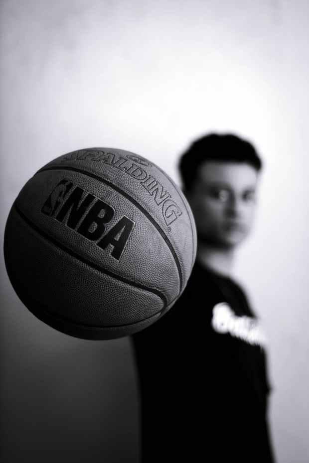 grayscale photo of man holding nba basketball