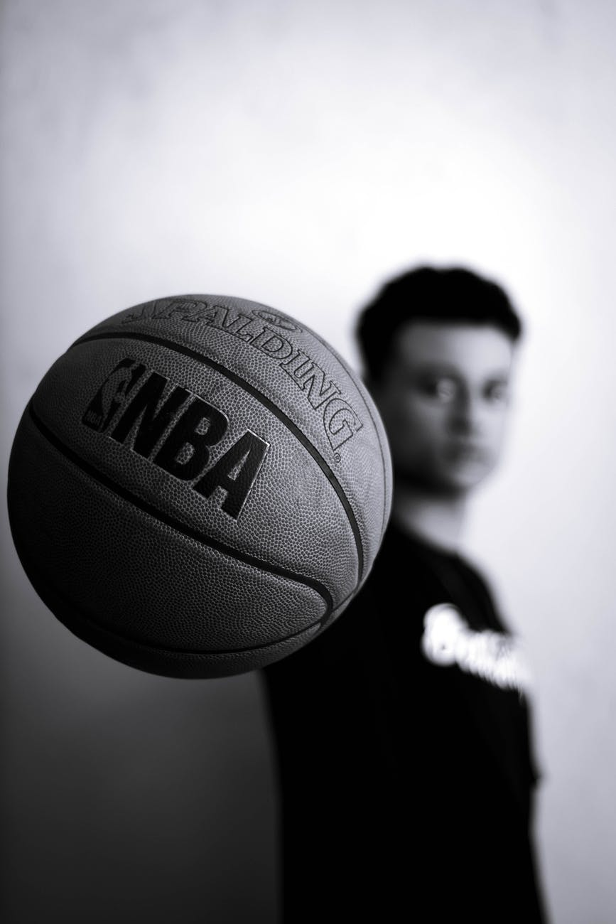grayscale photo of man holding nba basketball