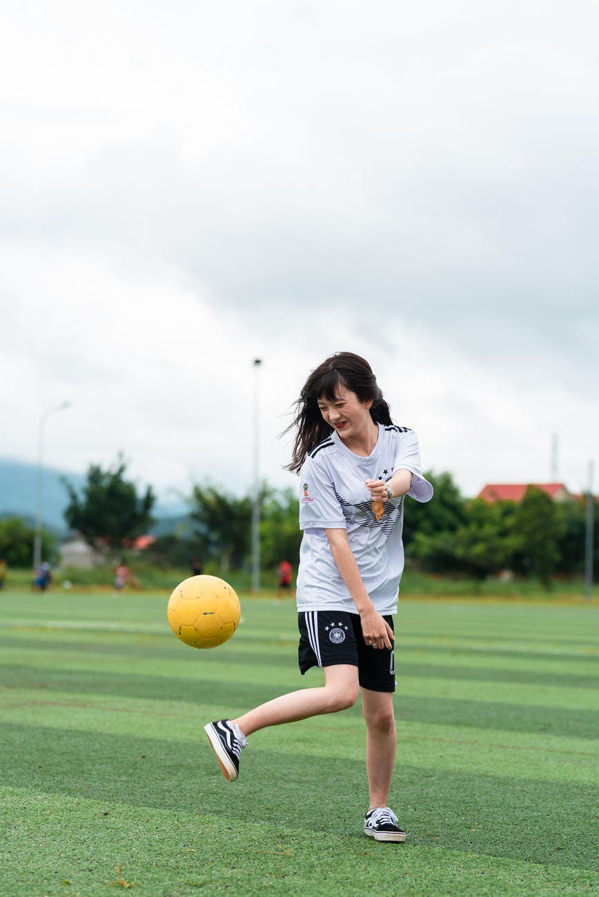 woman in white shirt and black shorts playing soccer