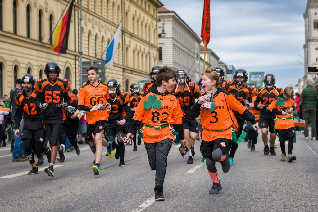 MUNICH, BAVARIA, GERMANY – MARCH 11, 2018: close up on running kids in American football clothes representing the Munich Rangers at the St. Patrick's Day Parade.