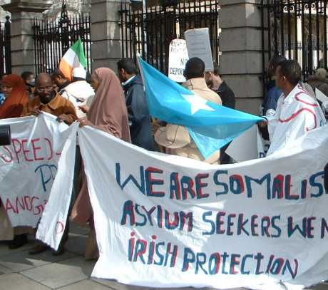 "A group of somali asylum seekers stand outside Dail holding up signs that read ""We are somali asylum seekers, we need irish protecction"""""
