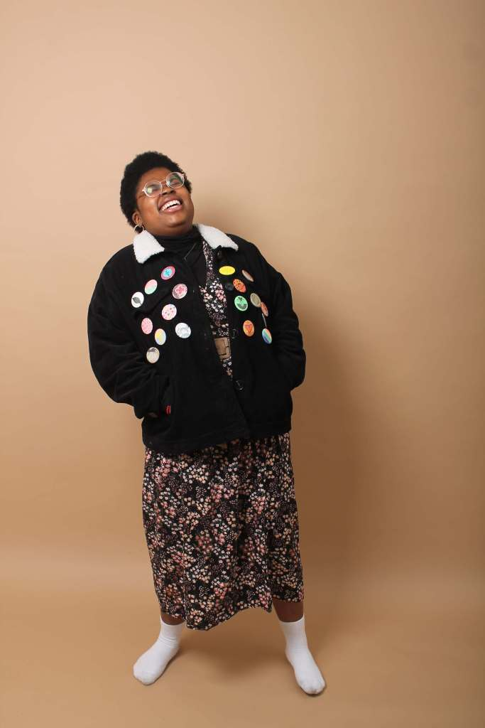One A non-binary black person n front of a beige backdrop under studio lights, wearing a patterned red, pink , white and black dress, with a brown belt, a black jacket with a white collar, covered in badges and white socks. The person is laughing with their eyes closed.