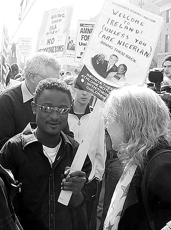 "Black and White photo of a man wearing sunglasses and holding up a sign that says ""welcome to Ireland. Unless you are Nigerian"""