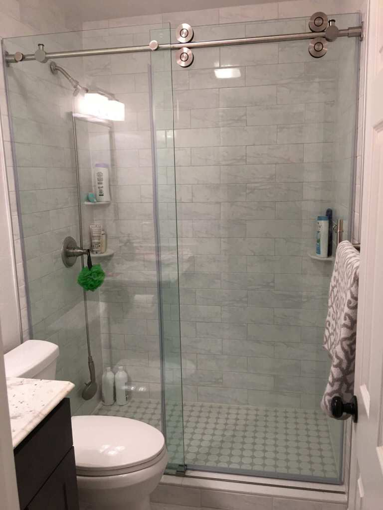 Bathroom remodeled with new wall and floor tile, shower tile, granite counters, vanity, paint, lights, mirror, and toilet.