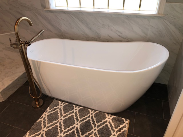 New stand-alone tub with custom gold faucet.