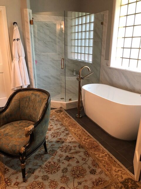 A bathroom remodeled with new shower and floor tile, new shower glass, new stand-alone tub, and new granite.