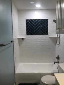 New bathroom with painted walls, resurfaced tub, LED lighting, and custom tile design in shower.