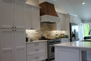 A kitchen remodeled with new grand island, cabinets, quartz counters, engineered wood floors, and painted walls.