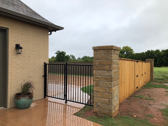 New stone pillars, cedar fence, and wrought iron gate.