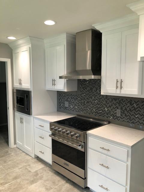 New porcelain tile floor, new backsplash, new custom cabinets and paint, new lighting, new appliances and vent hood.