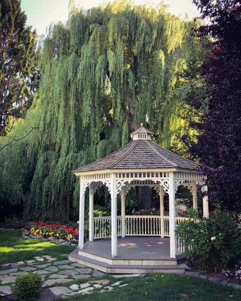 gazebo in garden under large willow tree