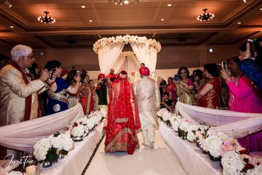 A father walks his daughter up a lavishly decorated wedding aisle to the mandap or wedding stage.