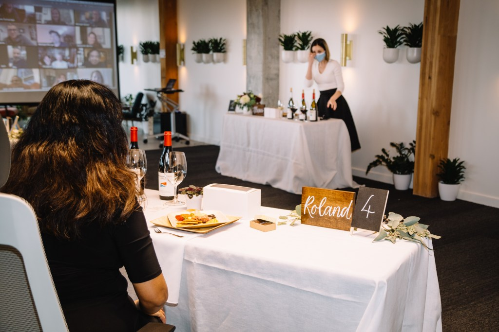 a hybrid event attendee listens to a sommelier from a distant table