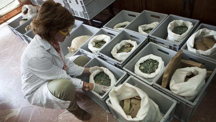 Una mujer abre una bolsa repleta de monedas de bronce romanas, Museo Arqueológico de Sevilla, España, 28 de abril de 2016.
