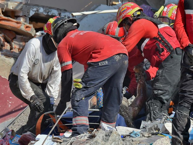 Rescuers remove a corpse from the rubble in Manta, Ecuador on April 19, 2016, two days after the 7.8-magnitude quake that struck the region. Rescuers and desperate families clawed through the rubble Monday to pull out survivors of an earthquake that killed at least 413 people and destroyed towns in a tourist region of Ecuador. / AFP PHOTO / LUIS ACOSTA