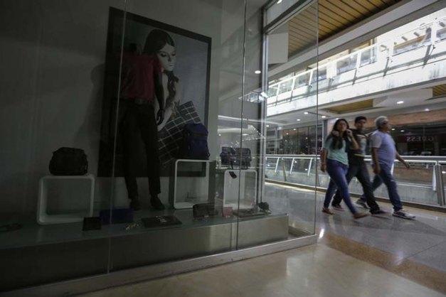 Unas personas pasan frente a una tienda cerrada en un centro comercial de Caracas, feb 10, 2016. Venezuela inició esta semana un plan de cortes de electricidad para restringir el consumo hasta que comience la temporada de lluvias, indispensables para que las plantas hidroeléctricas que generan un 60 por ciento de la energía del país recuperen su funcionamiento pleno. REUTERS/Marco Bello