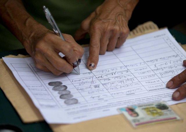 Una persona firma una petición, organizada por la oposición, para iniciar un referendo revocatorio del mandato del presidente de Venezuela Nicolás Maduro en San Cristóbal, el miércoles 27 de abril de 2016. (Foto AP / Fernando Llano)