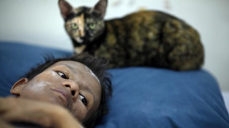Una mujer tailandesa enferma de sida junto a su gato se hospeda en el templo budista Wat Prabat Nampu en Lopburi