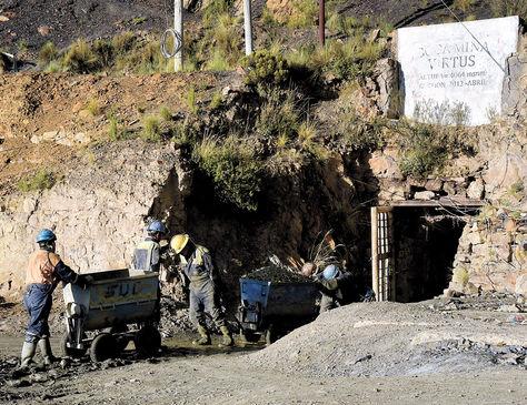 Mineros sacan carros llenos de roca en la bocamina Virtus de Amayapampa.