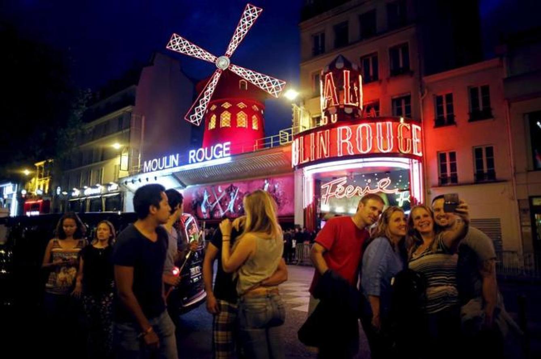 Turistas frente al Moulin Rouge de París, en julio de 2015 (Reuters)