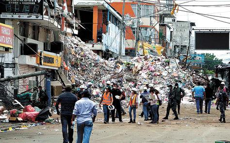 Destrucción. Escombros en media calle flanquean edificios afectados en el barrio Tarqui, en la ciudad de Manta, al norte del Ecuador.  Foto: EFE