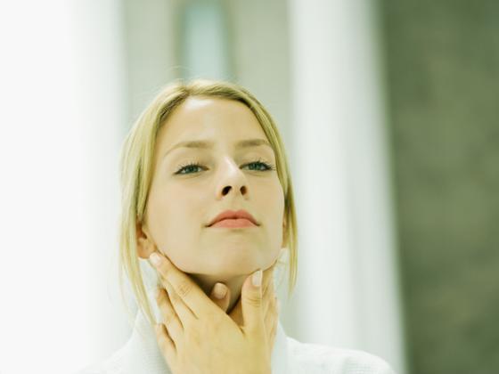 Una mujer joven se mira en el espejo.
