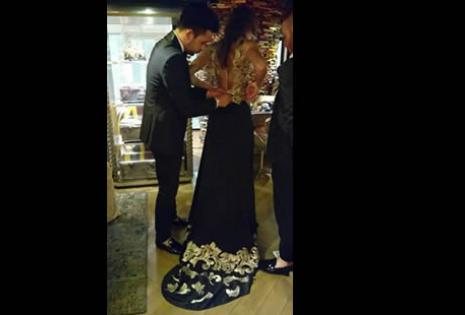 El diseñador acomodando los últimos detalles de un vestido en el que se destaca la cola