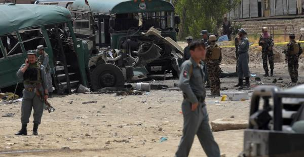 El personal de seguridad afganas se reúne cerca de los restos de los autobuses que llevaban cadetes de la Policía