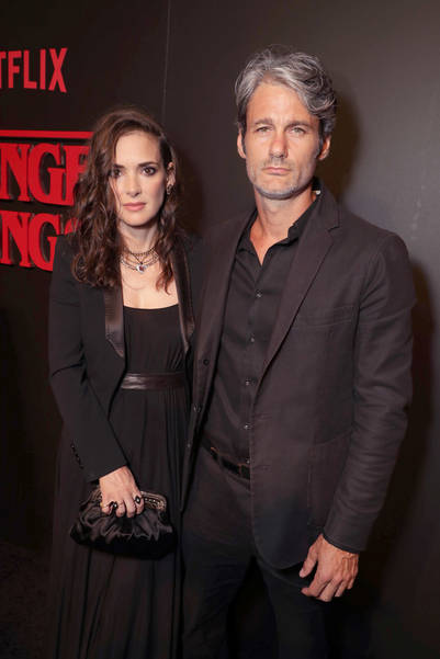 """Winona Ryder and Scott Hahn seen at the red carpet premiere in support of the launch of the Netflix original series """"Stranger Things"""" at Mack Sennett Studios on Monday, July 11, 2016, in Los Angeles, CA. (Photo by Eric Charbonneau/Invision for Netflix/AP Images)"""