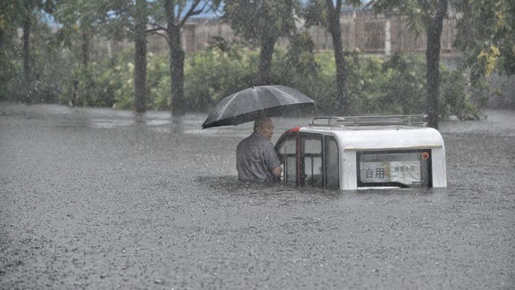 Un hombre bajo su paraguas cerca de su coche en la calle inundad de Pekín.