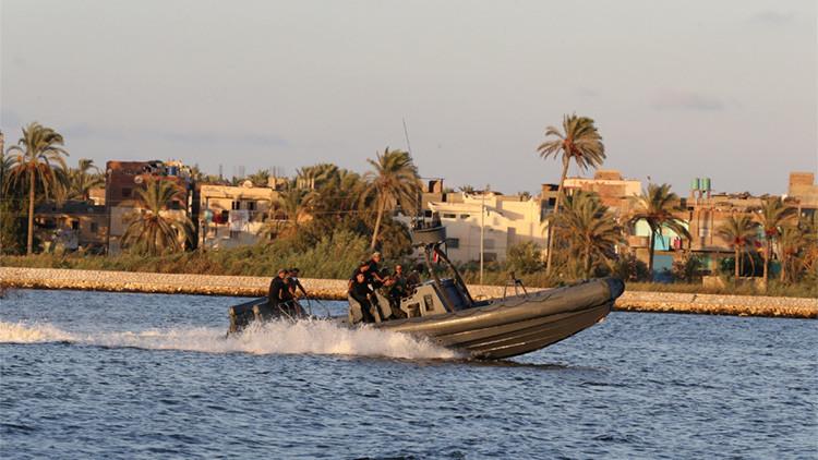 Una lancha militar transporta los cuerpos de las víctimas del naufragio frente a la costa egipcia.