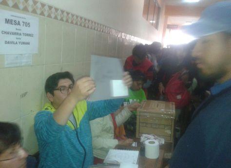 Un jurado de mesa muestra la papeleta de las elecciones de la UMSA.