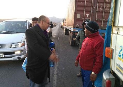 El ministro de Defensa, Reymi Ferreira, conversa con un transportista afectado por el paro de trabajadores chilenos en frontera