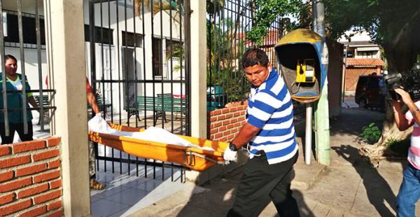 Efectivos de la división de Homicidios retiran el cuerpo del chico del centro de salud municipal San Luis, cerca de la av. 26 de Febrero