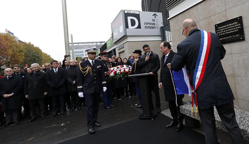 El presidente francés, François Hollande, coloca una placa dedicada a las víctimas fuera del Estadio de Francia en París