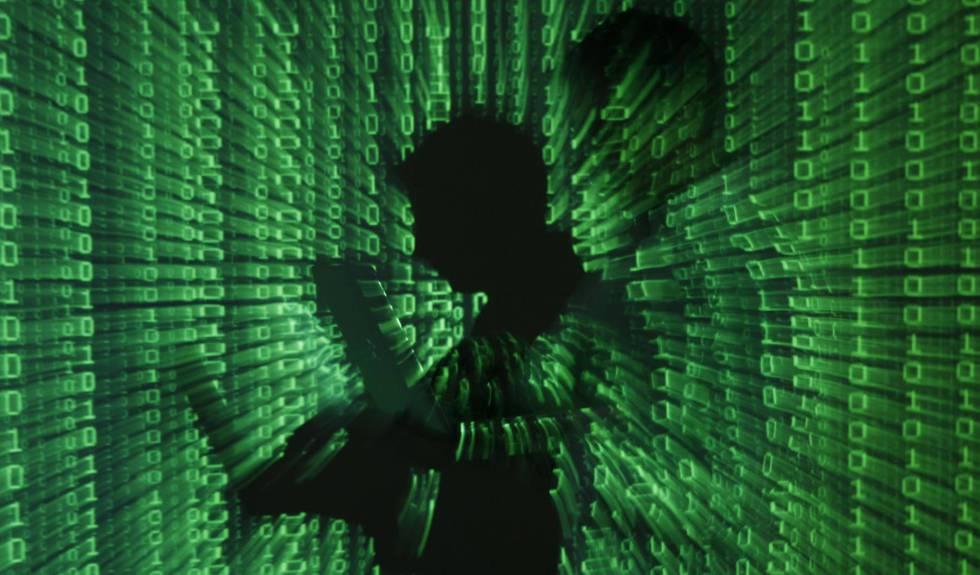 Un hombre sostiene un ordenador portátil con un fondo binario.