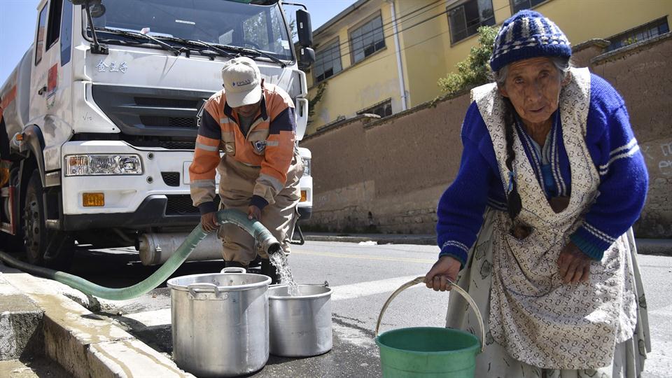 Una mujer junta agua en pequeños baldes para llevar a su casa. Foto: AFP / Aizar Ralde