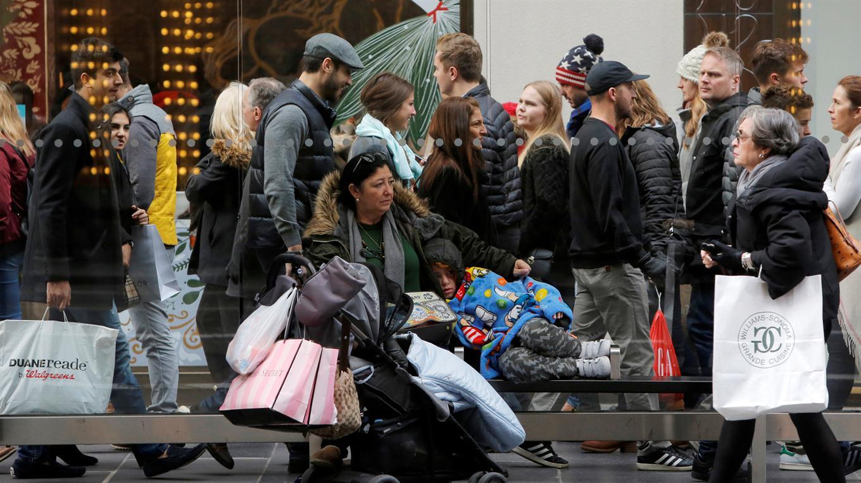 Una mujer y su hijo esperando el colectivo después de las compras. Foto: Reuters / Andrew Kelly