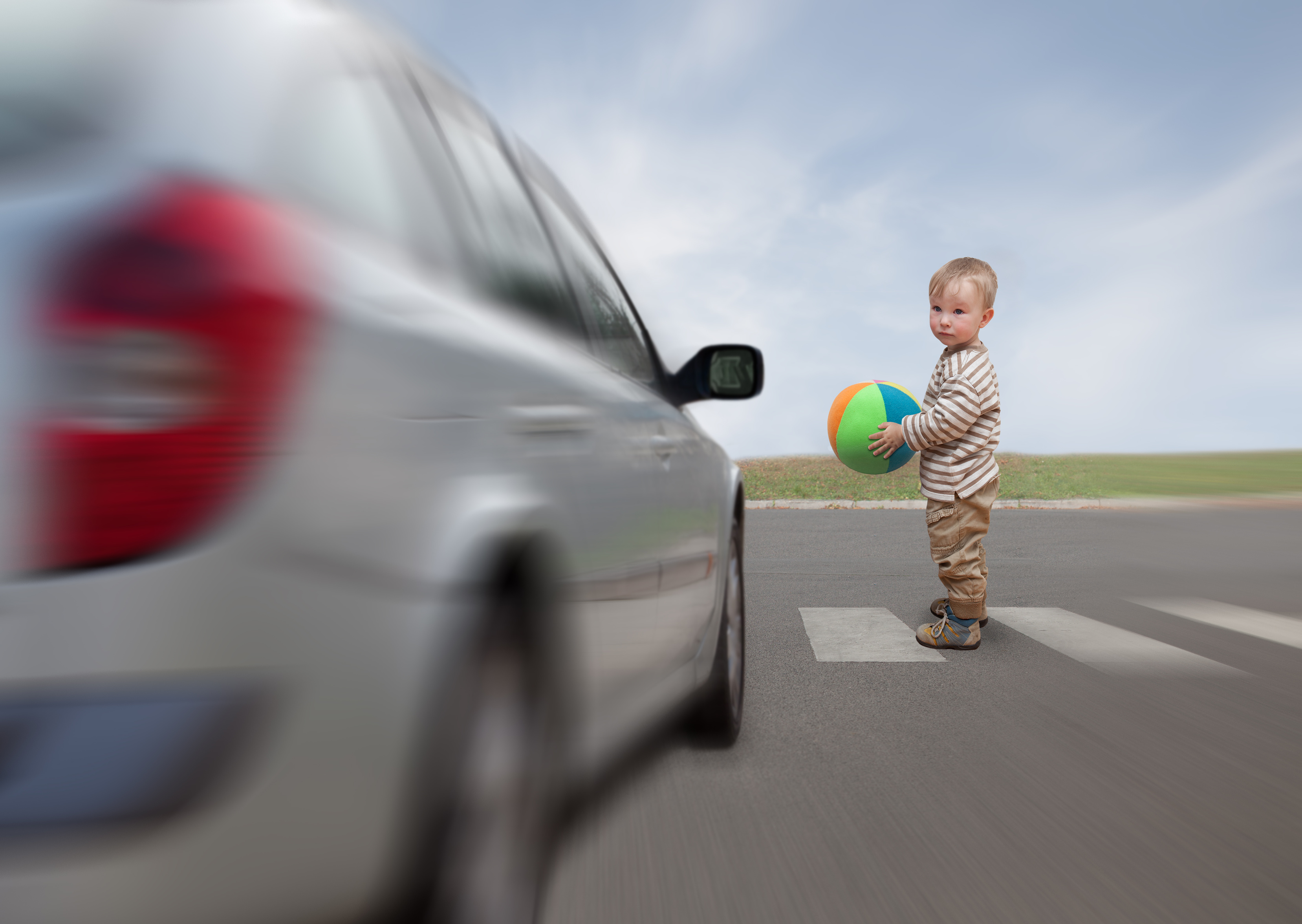 baby with ball tries to cross the road