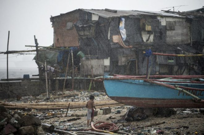 A boy runs for cover as it rains near the breakwater in Baseco, Manila on December 26, 2016. Typhoon Nock-Ten, which made landfall on the eastern island province of Catanduanes on December 25, is forecast to move westward towards the country