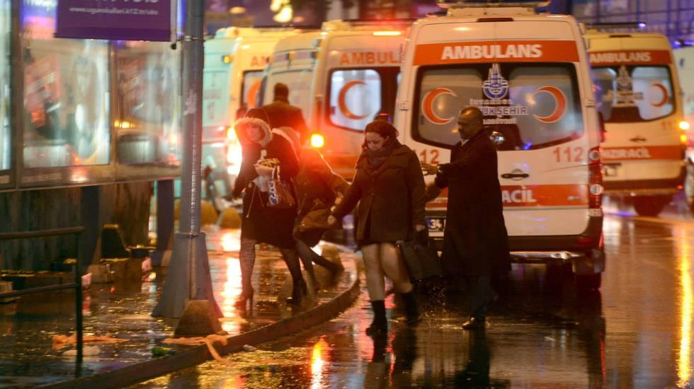 Personas huyendo del lugar del ataque junto a varias ambulancias. rn