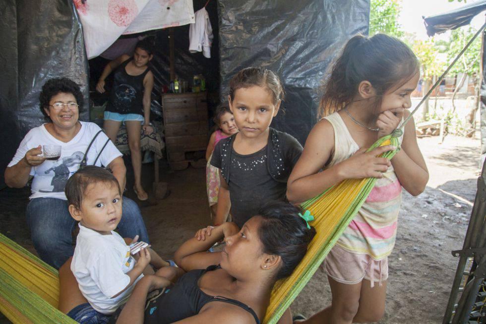 Paloma, nicaragüense de 17 años, en primer plano rodeada de sus hermanas y de Milagros, trabajadora social.