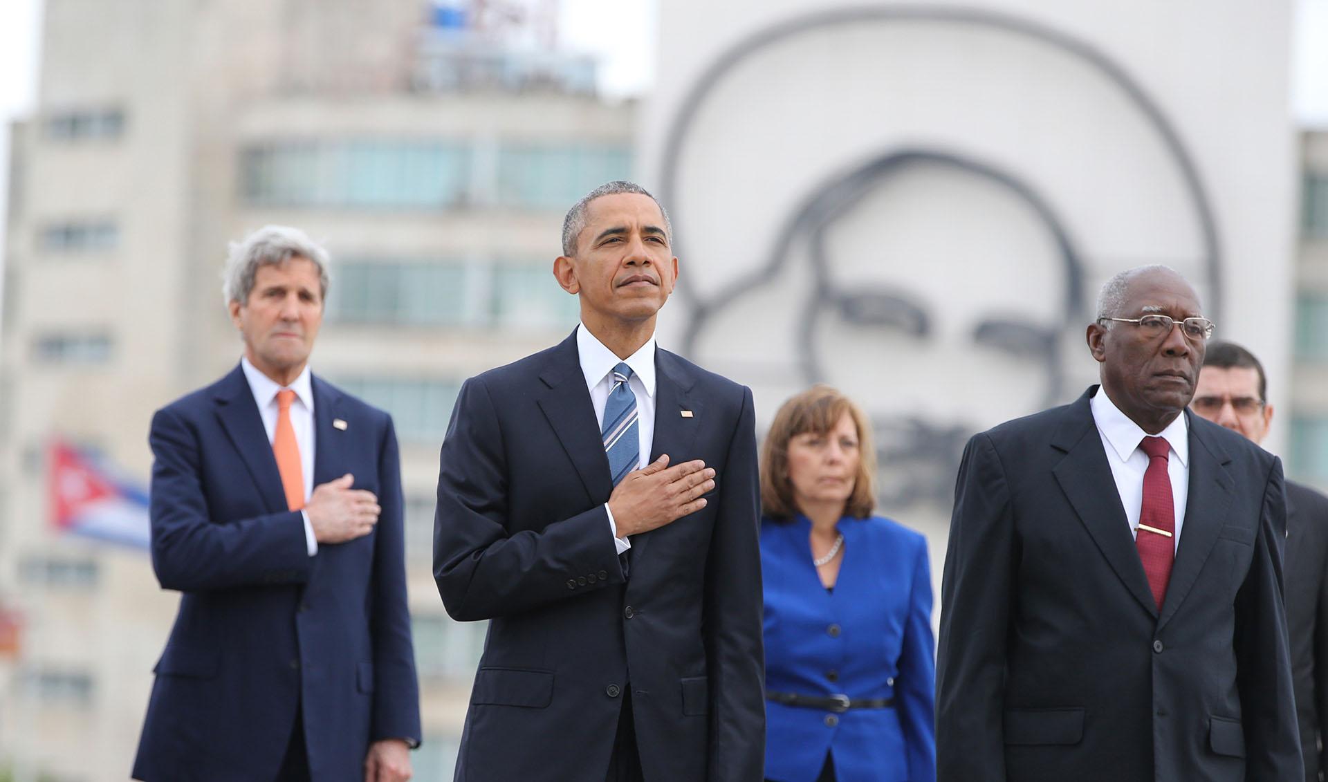 El presidente Barack Obama, y el secretario de Estado John Kerry, escuchan el himno nacional de EEUU durante una ceremonia en el monumento a José Martí en la Plaza de la Revolución en La Habana, Cuba, el lunes 21 de marzo de 2016. A la derecha está Salvador Valdés, vicepresidente del Consejo de Estado de Cuba. (Foto AP / Enric Martí)