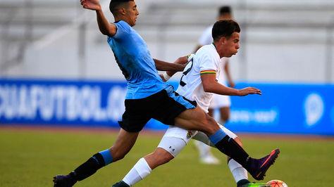 El jugador uruguayo Carlos Nahuel Benavidez disputa el balón con el boliviano Henry Vaca.