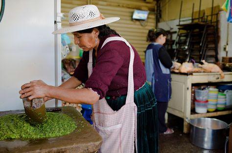 Una mujer prepara el llajwa, la salsa picante por la que se conoce a Bolivia, con una gran piedra redondeada. Foto: Christian Rodriguez-National Geographic Travel