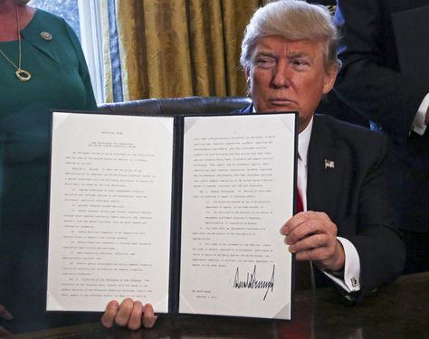 Donald J. Trump, enseña una orden ejecutiva firmada en el Despacho Oval de la Casa Blanca este 3 de febrero. Foto: EFE