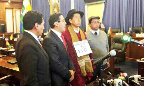 "Cusi luce un cartel que dice ""Sentenciado por Evo"". Junto a él sus abogados."